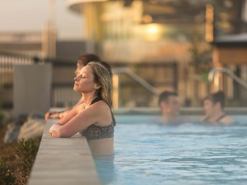 Profile view of a woman with a relaxed expression soaking in a hot pool
