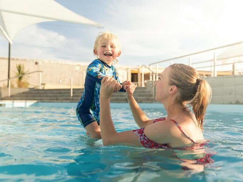 Woman and young boy playing together in a hot pool