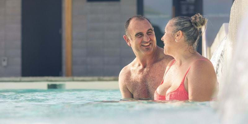 Man and woman talking while in a hot pool