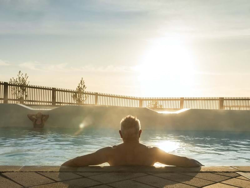 Man looking towards the sun while soaking in a hot pool